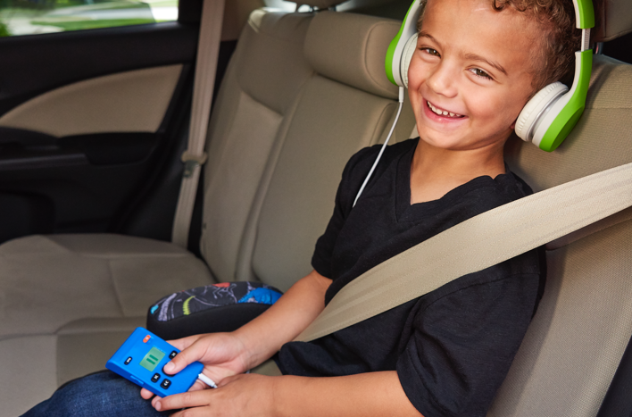 young child sitting in a car using a Playaway device